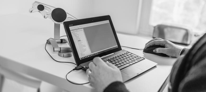Kvinna vid laptop förbereder webinar med QBIS