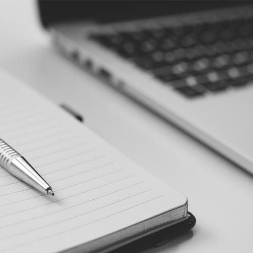 Dator och anteckningsblock, redo för QBIS webinar