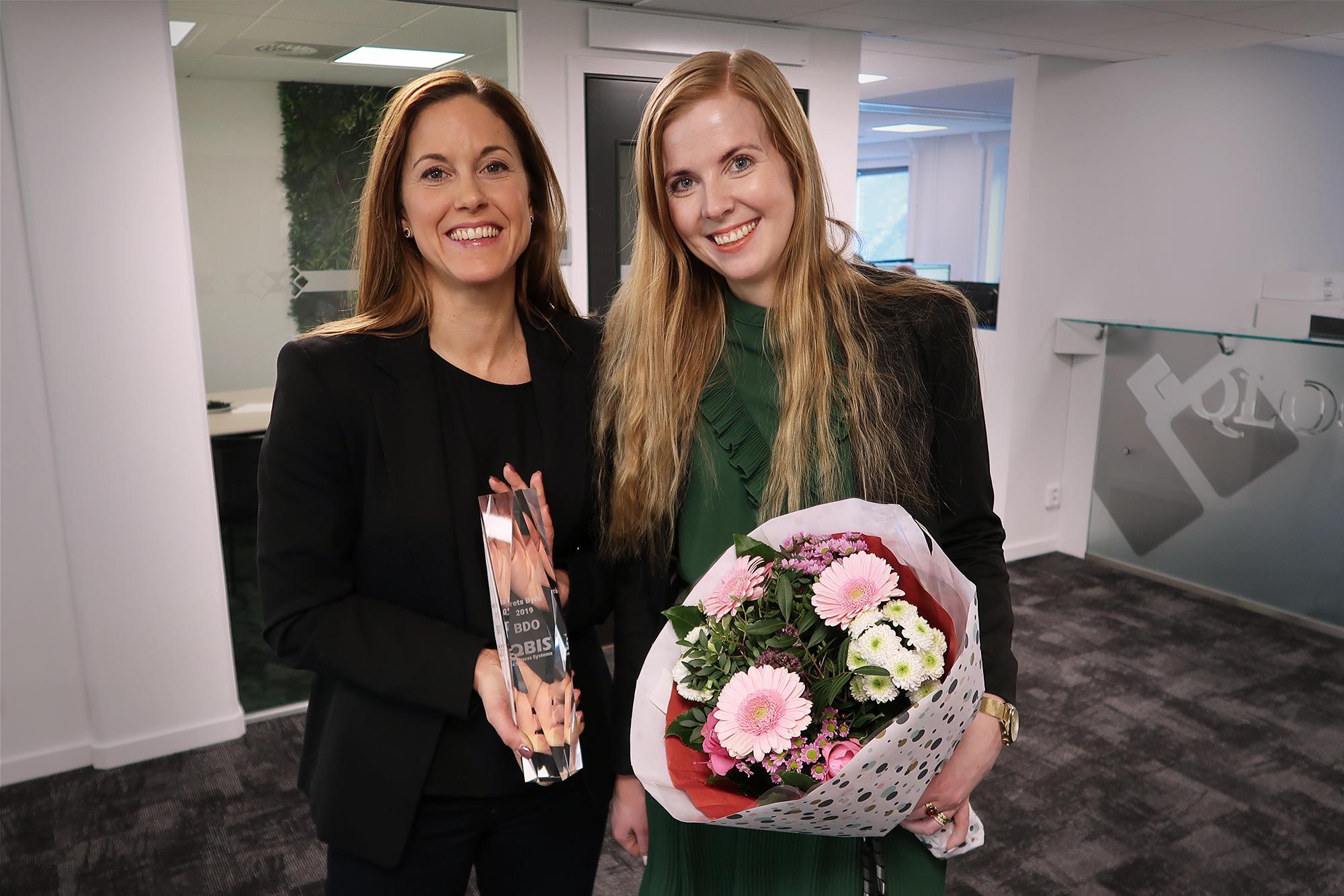 Två kvinnor med pris Årets Byrå och blombukett för QBIS Partner Awards